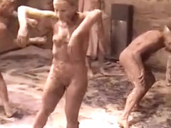 Naked female bodies covered in mud at art show